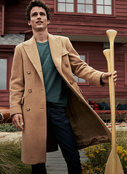 Man in camel overcoat & green T-shirt holds two wooden oars