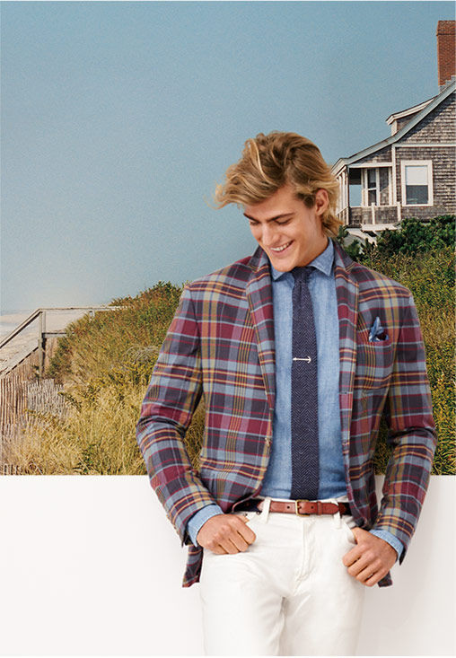 Man wears plaid blazer, chambray shirt, navy tie, silver tie pin and white pant; beach cottage and dune in background