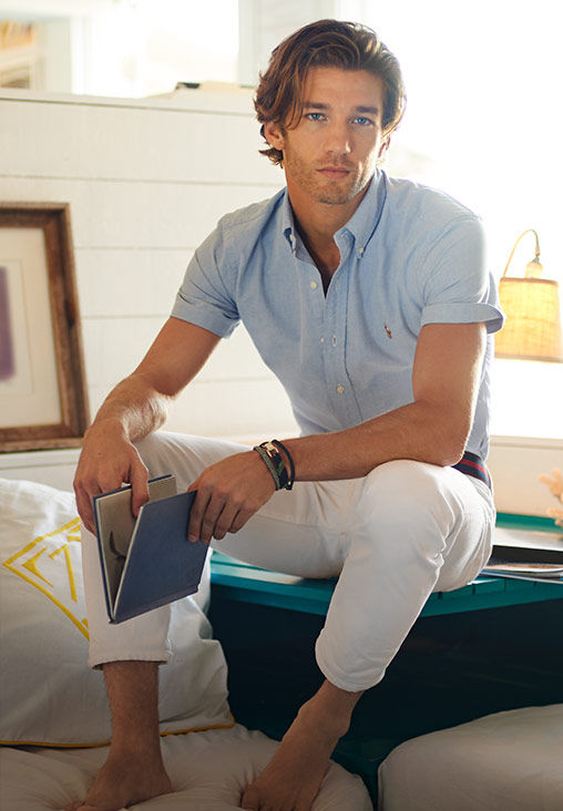 Man wearing chambray short-sleeve button-down shirt & white pant sits with book on  teal bench