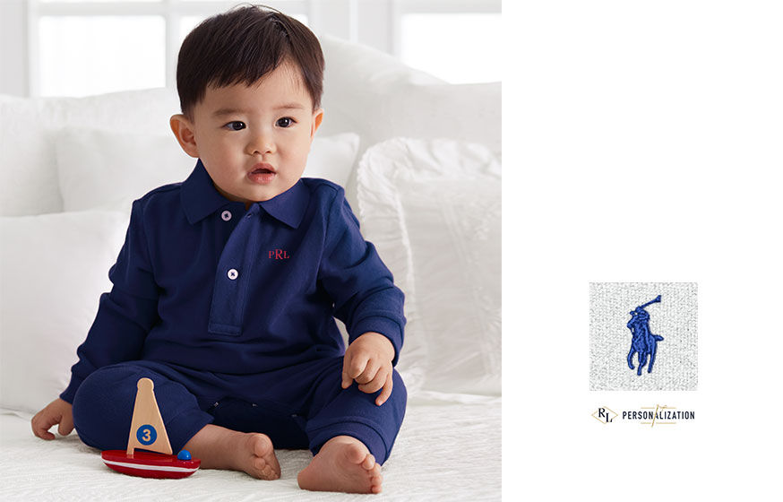 Left: Baby in long-sleeve coverall with Polo collar sits with toy boat. Right: Close-up of blue signature embroidered pony
