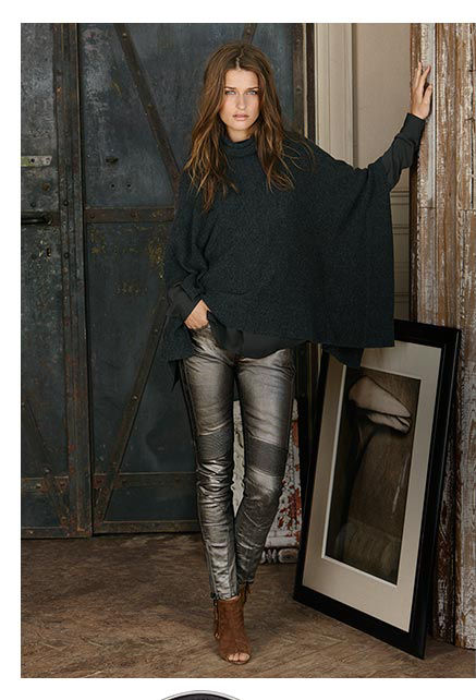 Woman in knit poncho & metallic skinny pant