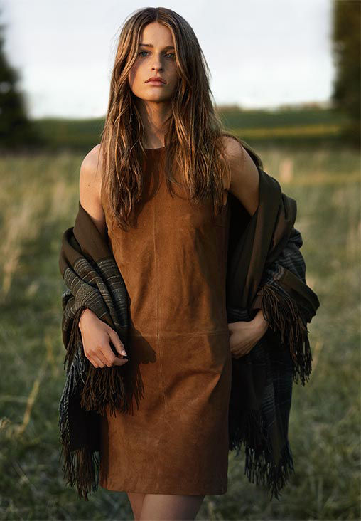 Video of woman walking through field in suede sheath dress with brown striped blanket around her shoulders
