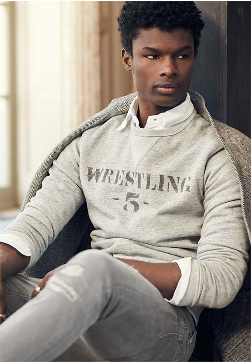 Man layers tweed jacket over grey sweatshirt with stencil-inspired wrestling text
