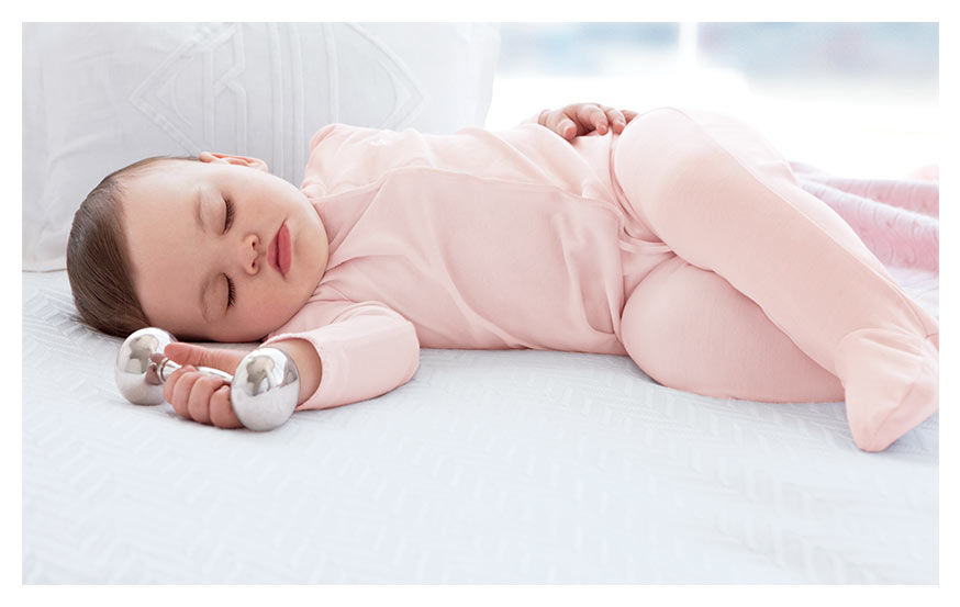 Sleeping baby wears pink coverall and holds silver rattle