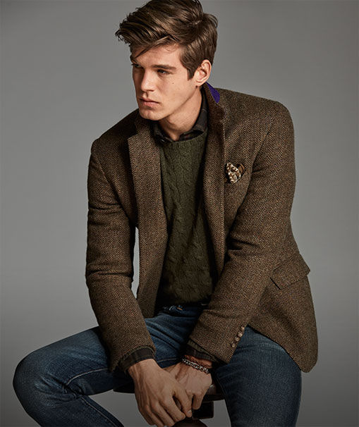Man models tweed jacket, green cable-knit sweater & jean