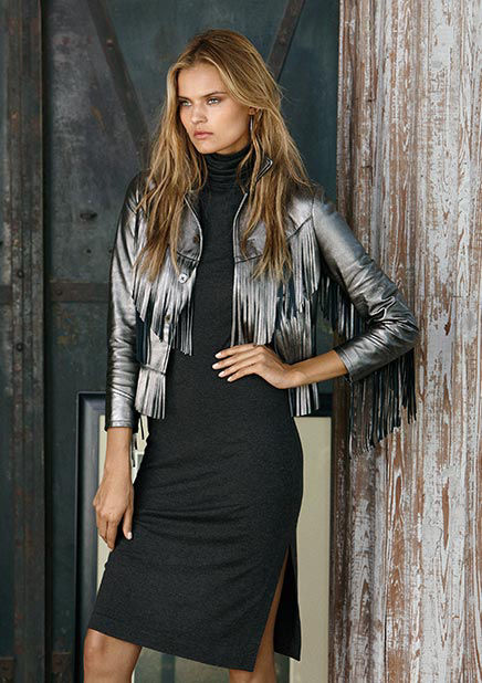 Woman layers silver-toned metallic fringed jacket over grey turtleneck dress