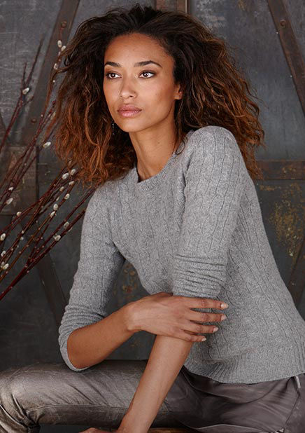 Woman models grey cable-knit sweater