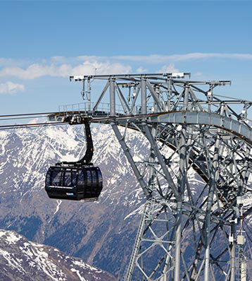 Ski gondola moves along cables in front of snow-covered mountains