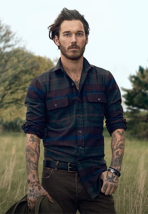 Man wears plaid button-down with brown jeans