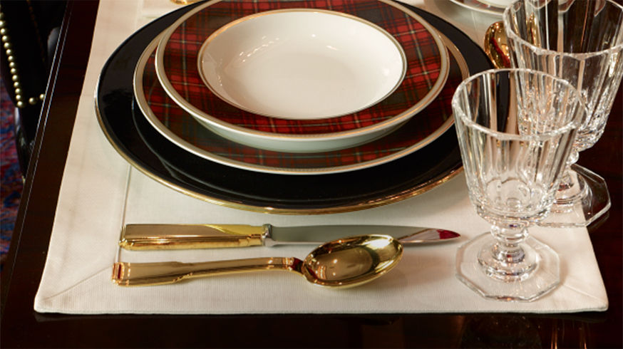 Place setting with gold-tone flatware, plaid-patterned dishes & stemmed glassware