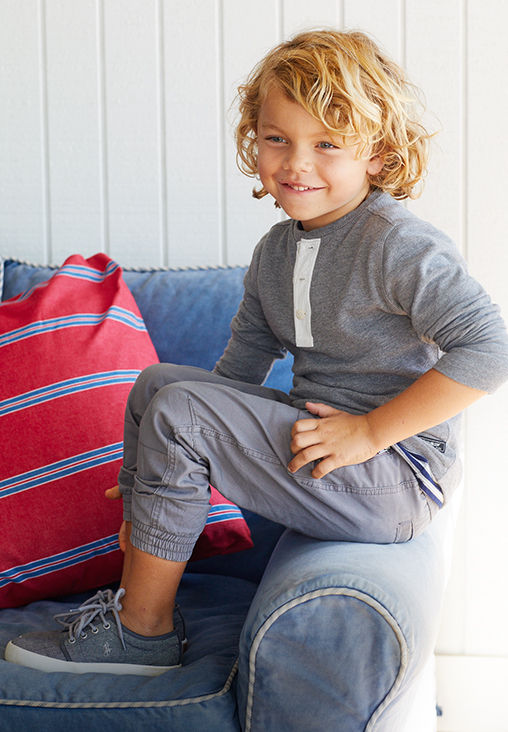 Boy wears grey long-sleeve tee with white placket and grey joggers.