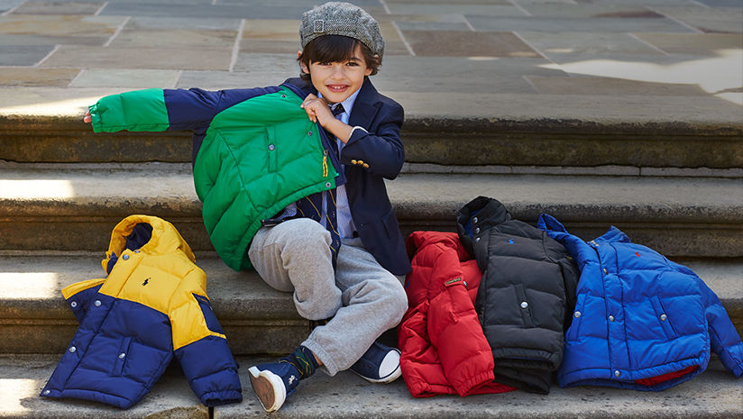 Boy puts on navy & green down jacket; assorted colorful jackets also shown.