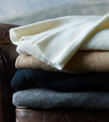Stack of cream, tan, black & grey sweaters