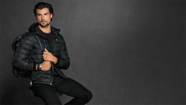 Man in black puffer jacket \u0026amp; black pants carries black backpack