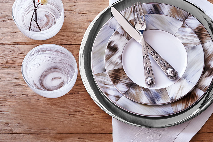 Place setting with horn-inspired motif & glasses with white swirling pattern