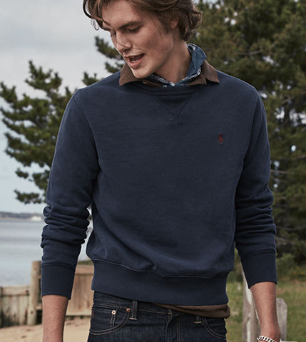 Man on beach in navy crewneck sweater
