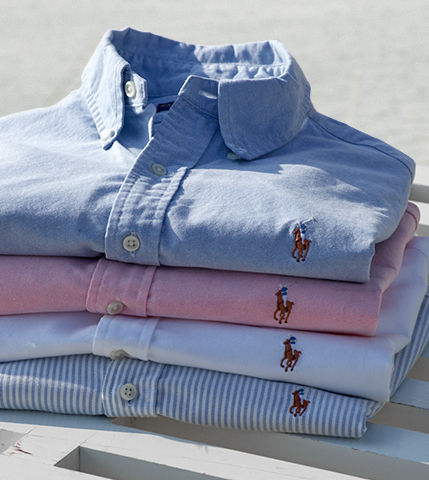 Stack of folded button-downs in light shades of blue, white & pink